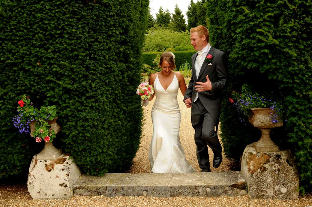 A great shot on the move of the wedding couple as they come through the gap in the hedge engaged in converstion at Hartsfield Manor