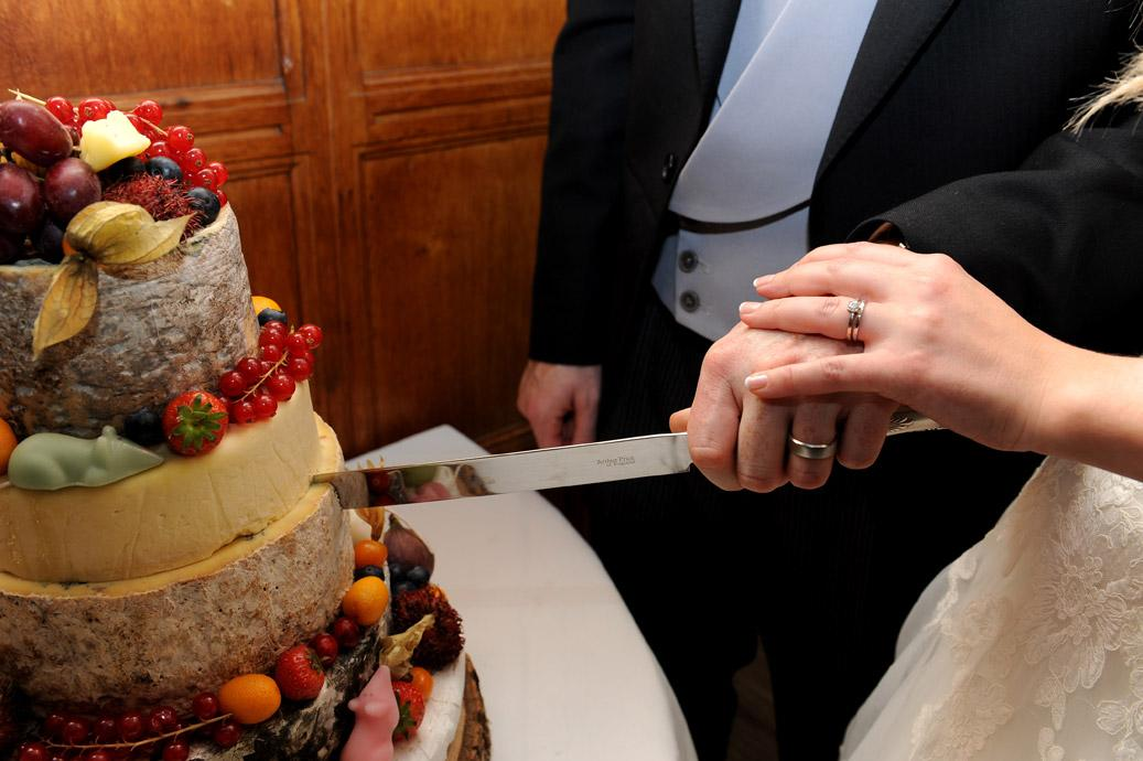 Close up wedding photo of the bride and Groom's hands as they cut the sumptuos cheese and fruit wedding cake taken in the large hallway at Hartsfield Manor in Betchworth Surrey