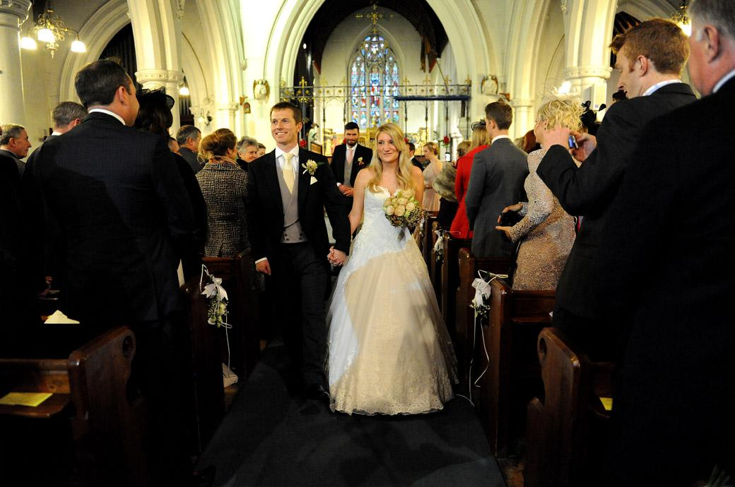 Delighted Bride and Groom walk down the church aisle as husband and wife taken by a Surrey Lane wedding photographer before leaving for the reception at Hartsfield Manor