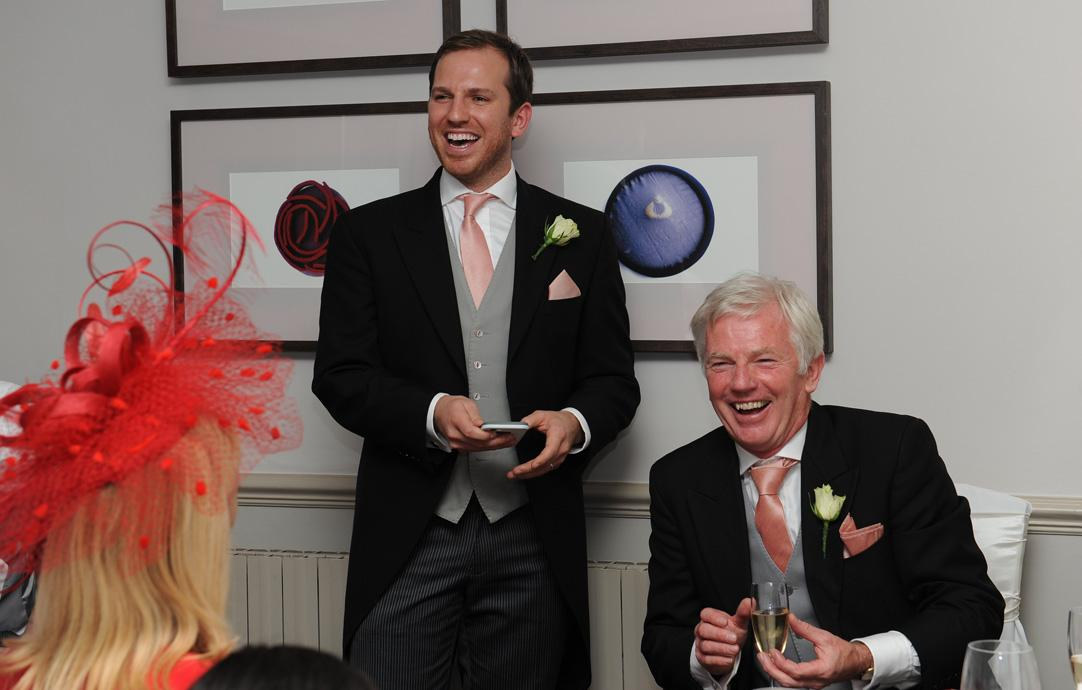Laughing speakers as they deliver some funny lines during the speeches during the wedding breakfast at Hartsfield Manor a wedding venue in Betchworth Surrey