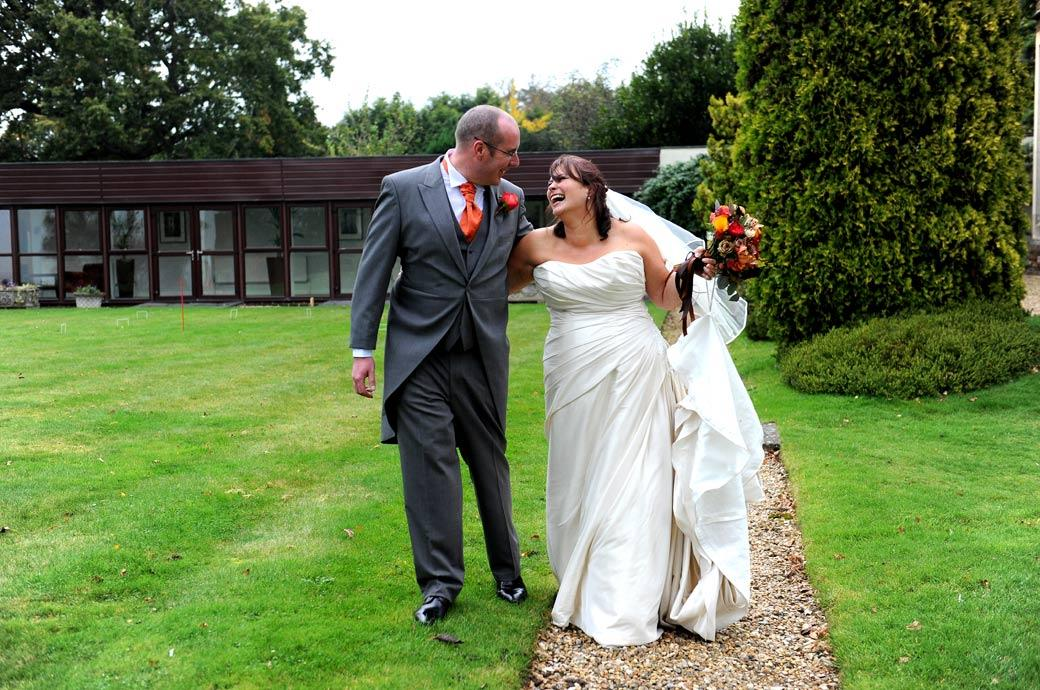 Happy carefree Bride laughing in this wedding photo as she walks along the path with her husband at welcoming Surrey wedding venue Hartsfield Manor, Betchworth