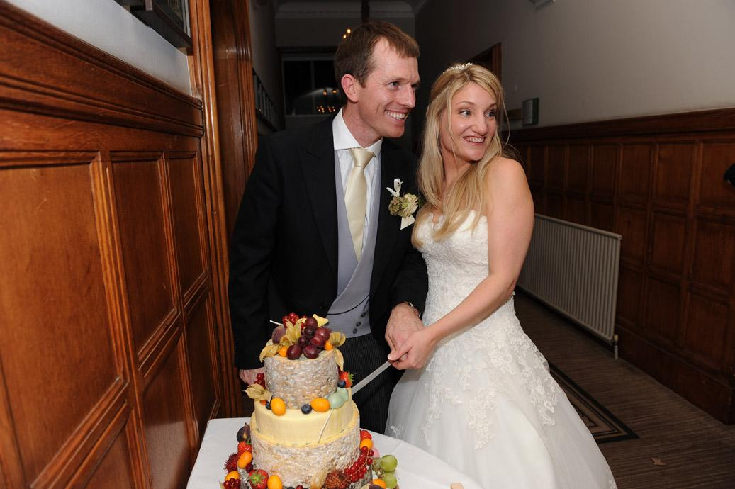 Bride and Groom smile for the Surrey Lane wedding photographers at  Hartsfield Manor, Betchworth as they cut their colourful and sumptuous cheese and fruit wedding cake