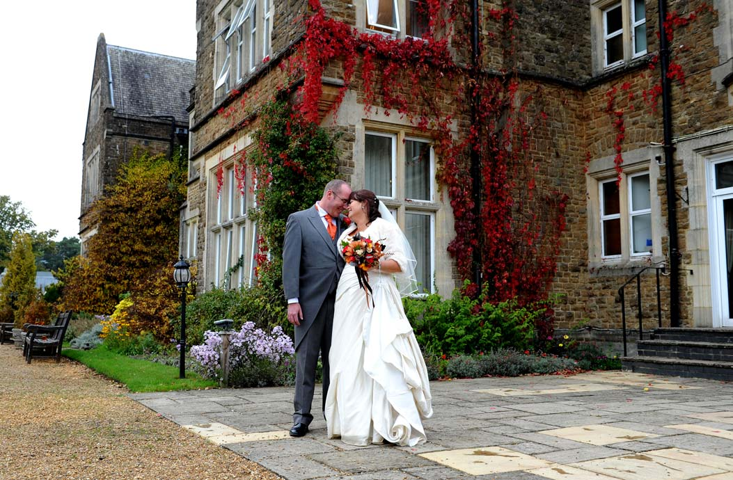 Wedding photo of smiling newlyweds standing in the garden in front of the impressive and colourful  Surrey wedding venue Hartsfield Manor resting their heads together