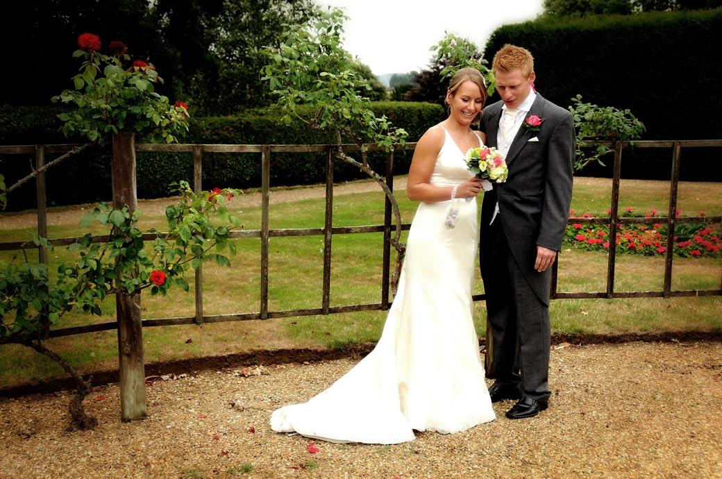 A romantic wedding photograph of the lovers in the rose garden admiring the bouquet at a wedding in Hartsfield Manor Surrey