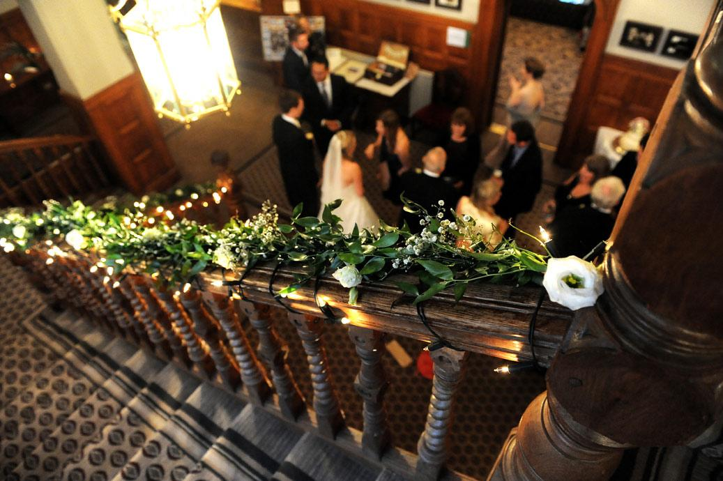 View from the top of the stairs looking over a flower covered banister at Surrey wedding venue Hartsfield Manor of the Bride and Groom at the end of the receiving line