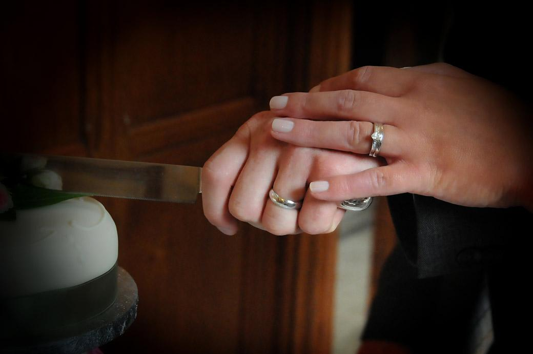 A cutting the cake wedding picture revealing the couples wedding rings taken at Surrey wedding venue Hartsfield Manor, Betchworth