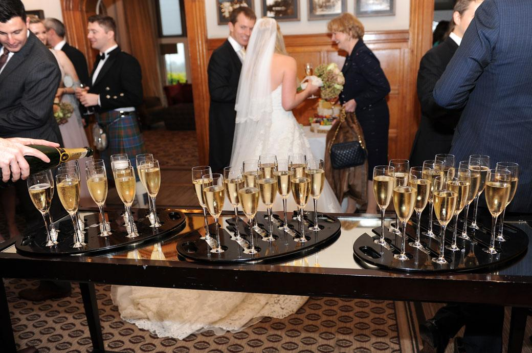 Trays of champagne being poured in the grand hall in this wedding picture taken at Surrey wedding venue Hartsfield Manor, Betchworth after a marriage ceremony in the Terrace Room