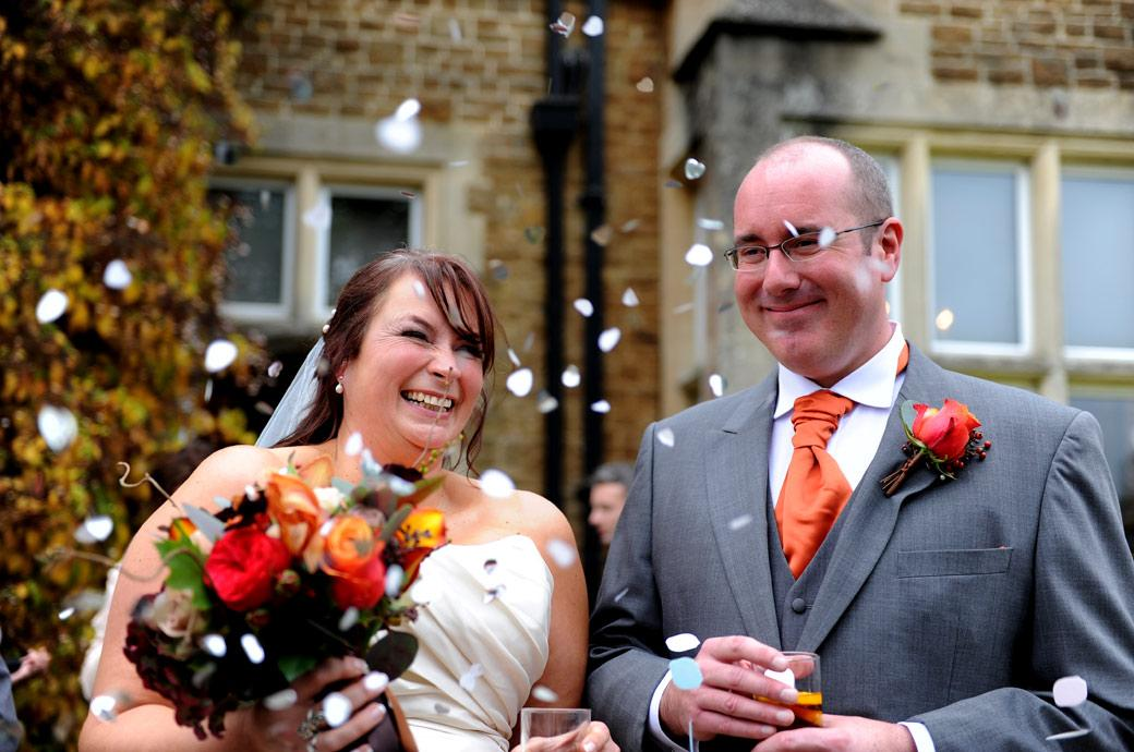 Bride and groom caught out by an unexpected shower of confetti as they stand out on the patio at Hartsfield Manor, Betchworth a comfortable and relaxed wedding venue in Surrey