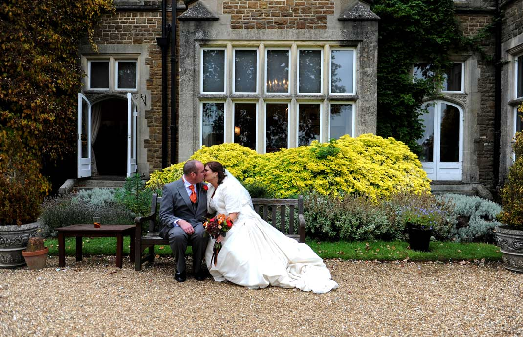 Wedding photo of newlyweds  romantically kissing on a bench in the pretty garden at Hartsfield Manor in Betchworth a relaxed and welcoming Surrey wedding venue