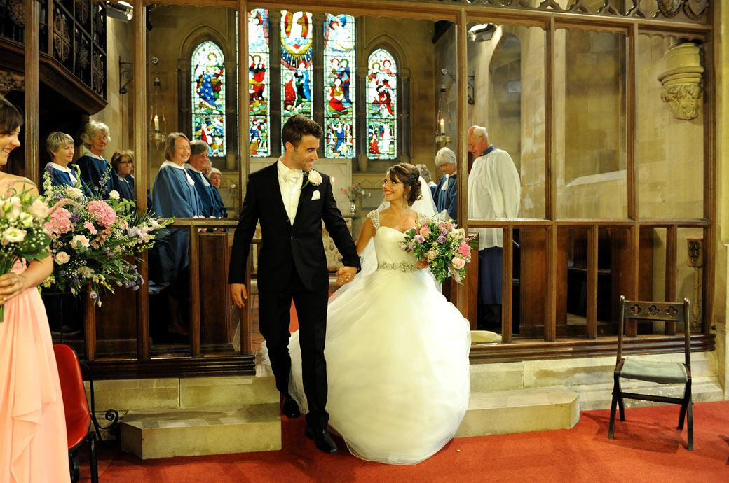 A delighted Bride looks excitedly over to her smiling Groom in this wedding photograph taken down the aisle of the Kent wedding venue St Paul's Church Four Elms