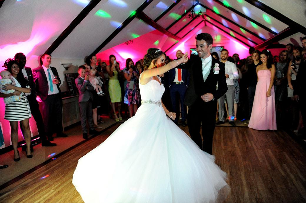 A Surrey Lane weding photographer captures the Groom smiling as he twirls his wife around the dancefloor during their first dance at Kent wedding venue Hever Castle Golf Club