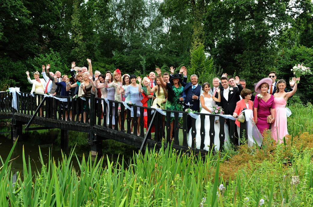 A waving family group wedding photo taken by Surrey Lane wedding photography on the lovely ornamental pond bridge at the relaxed and picturesque Hever Castle Golf Club in Kent