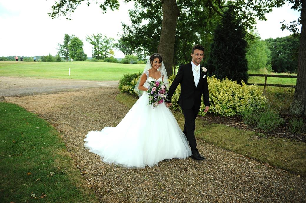 Happy smiling Bride and Groom captured in this wedding picture as they walk down the path towards the bridge at Kent wedding venue Hever Castle Golf Club by Surrey Lane wedding photography