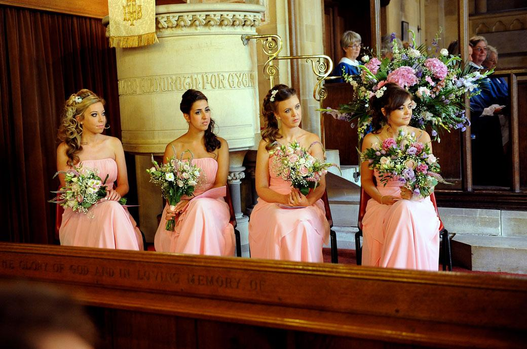 Bridesmaids listening to the marriage ceremony in  this wedding photo taken at St Paul's Church Four Elms before a reception at Kent wedding venue Hever Castle Golf Club