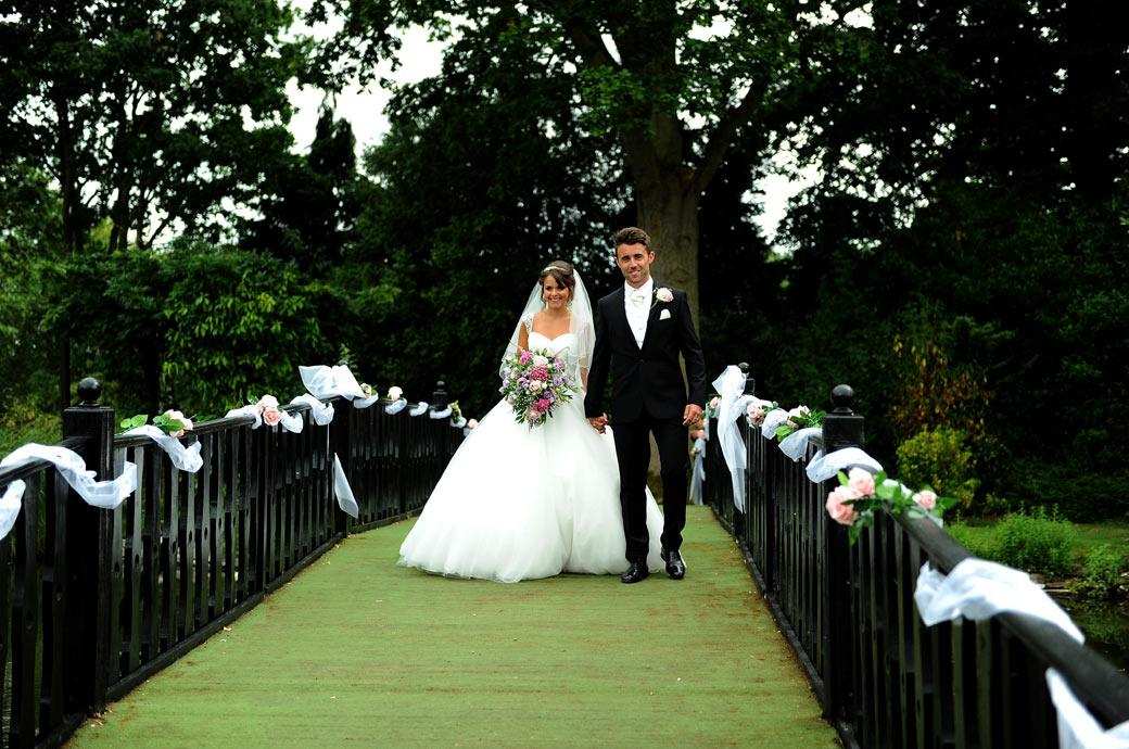 Smiling newly-wed couple walk across the bridge over the ornamanetal pond at Hever Castle Golf Club to meet guests captured in this wedding photograph by Surrey Lane photographers