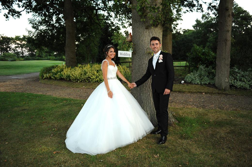 Excited newly-weds standing by the wedding sign in this wedding photo taken at the start of the path under the arbour at Hever Castle Golf Club in Kent
