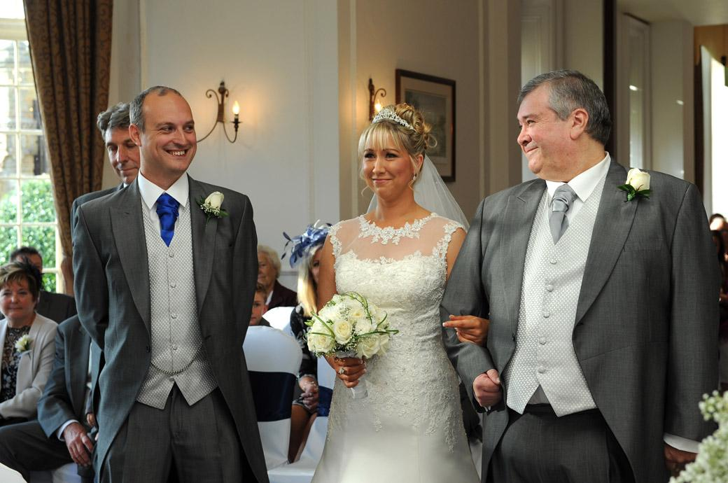 All smiles in this lovely relaxed wedding photograph taken by a Surrey Lane wedding photographer as the Bride and Father meet the Groom in the Sopwith Room at Horsley Towers