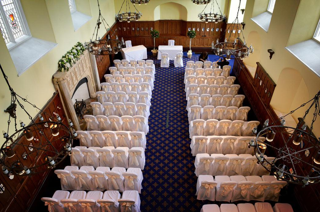 A view from the balcony of the ceremony room dressed and set up ready foe guests in the Great Hall in this ariel wedding picture at  Horsley Towers  a wonderful Surrey wedding venue