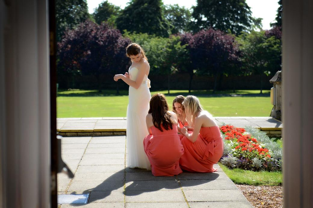 A peek through the door wedding photo taken from the Sopwith room capturing the Bridesmaids helping adjust the Bride's dress at Surrey wedding venue Horsley Towers