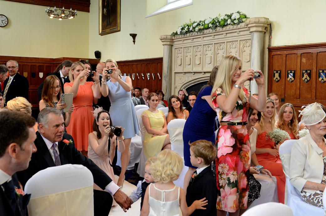 Fun and excitement as the guests get a chance to photograph the happy couple in this wedding picture from Surrey wedding venue Horsley Towers taken in the Great Hall