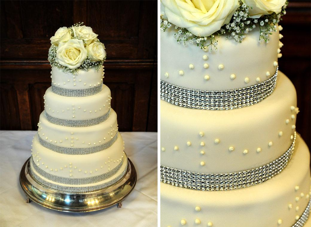 Elegant four tiered wedding cake topped with yellow roses as captured in these wedding photographs taken in Surrey in the Grand Hall  at Horsley Towers