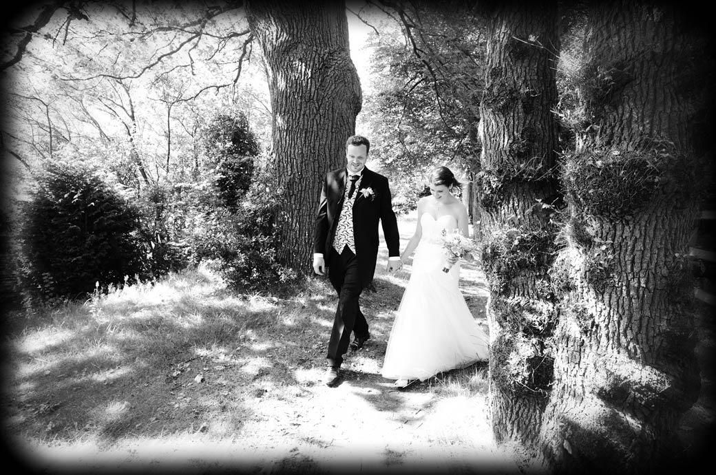A lovely fresh natural looking wedding picture of the happy young Bride and Groom walking through woods hand in hand at the magical Surrey wedding venue Horsley Towers