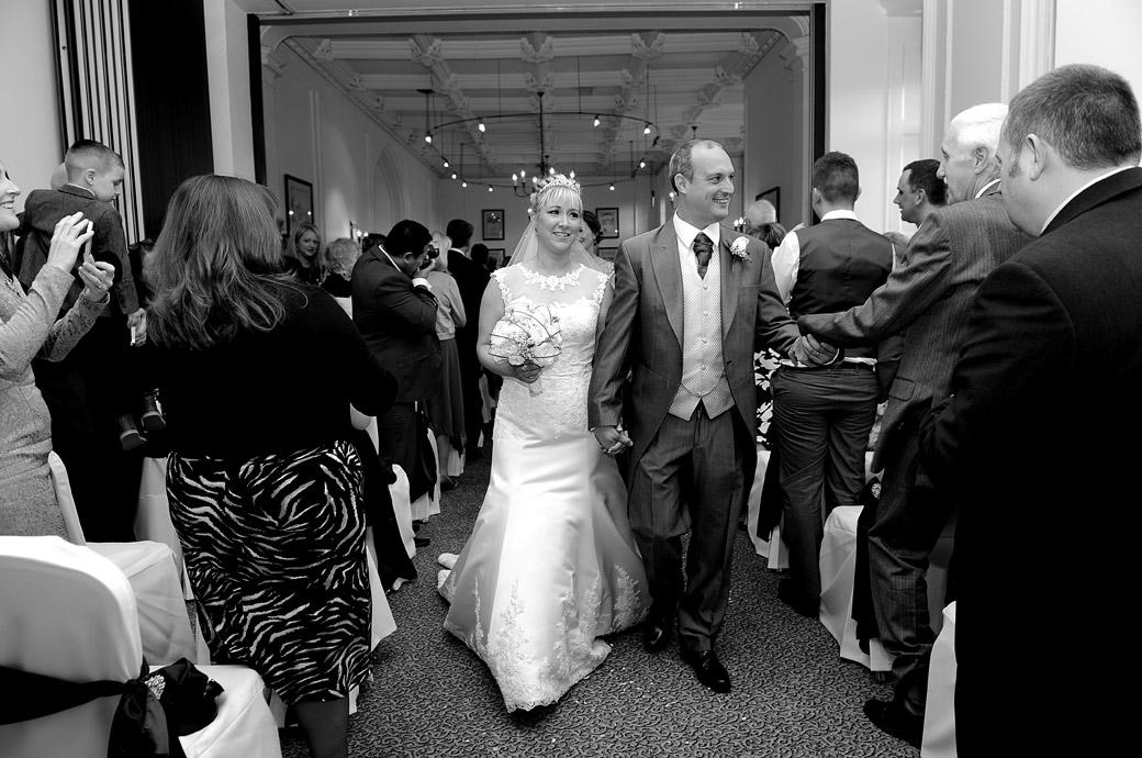 A joyful couple walk down the aisle as husband and wife captured in this wedding picture taken  in the Sopwith Room at Horsley Towers a wonderfully eccentric Gothic Surrey wedding venue