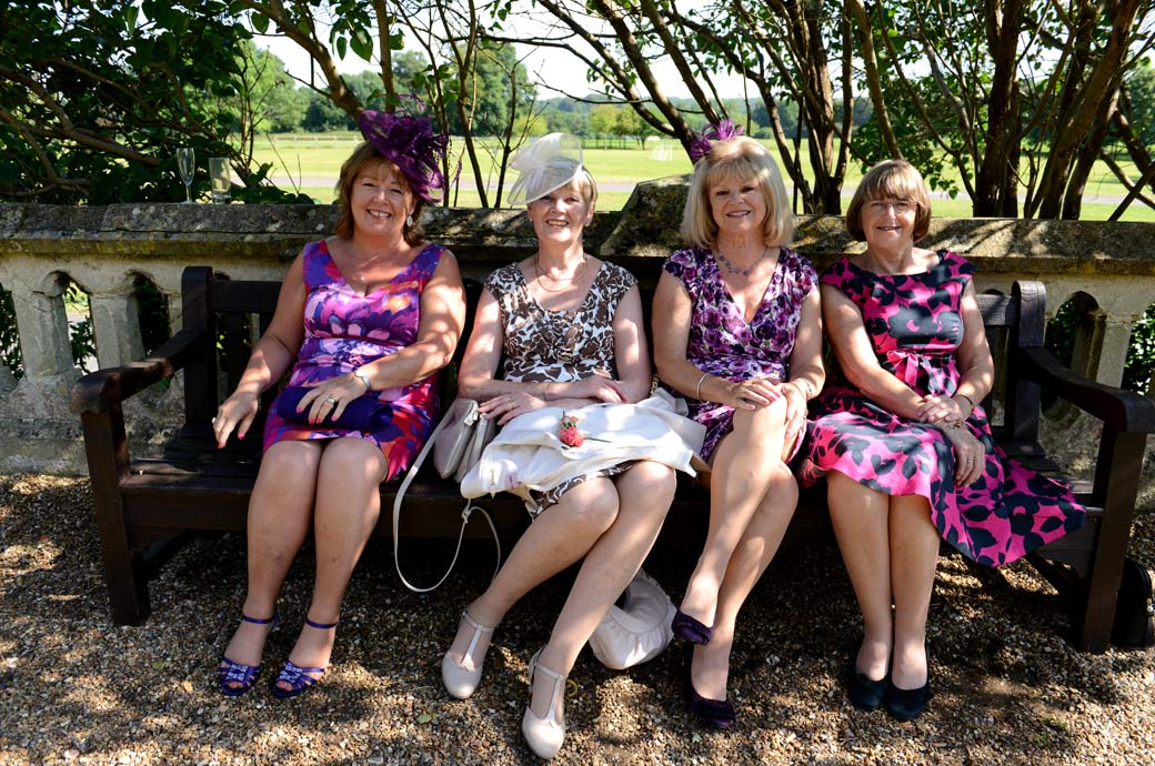 Lovely smiling ladies sitting on a bench in their colourful summer dresses in this wedding photo taken at the wonderful Surrey wedding venue Horsley Towers