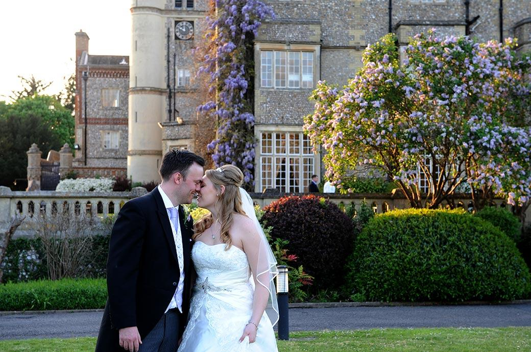 Loving happy moment captured in the tranquil grounds at Surrey wedding venue Horsley Towers as the Bride and groom rest their foreheads on each other