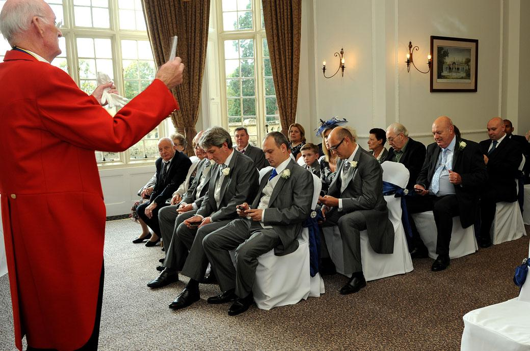 The  Master of Ceremonies in his distinctive red jacket captured in this wedding photograph telling all the guests to switch off their mobile phones at Horsley Towers a fine Surrey wedding venue