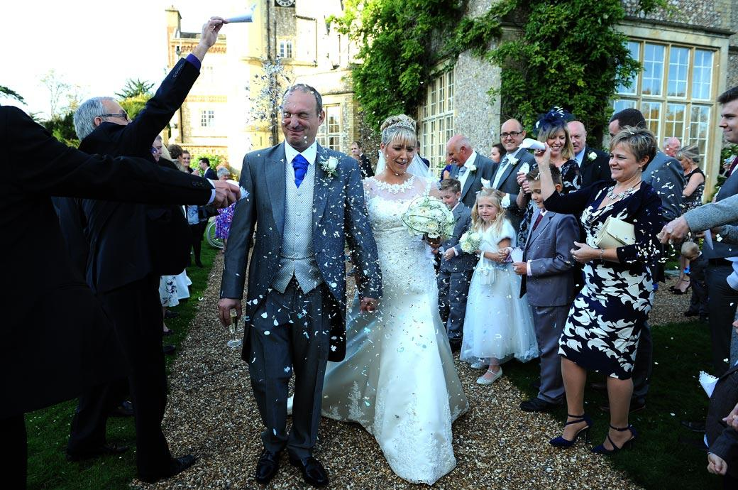 Bride and Groom with eyes closed nearing the end of the confetti line in this funny wedding photograph captured in the grounds of Horsley Towers in Surrey