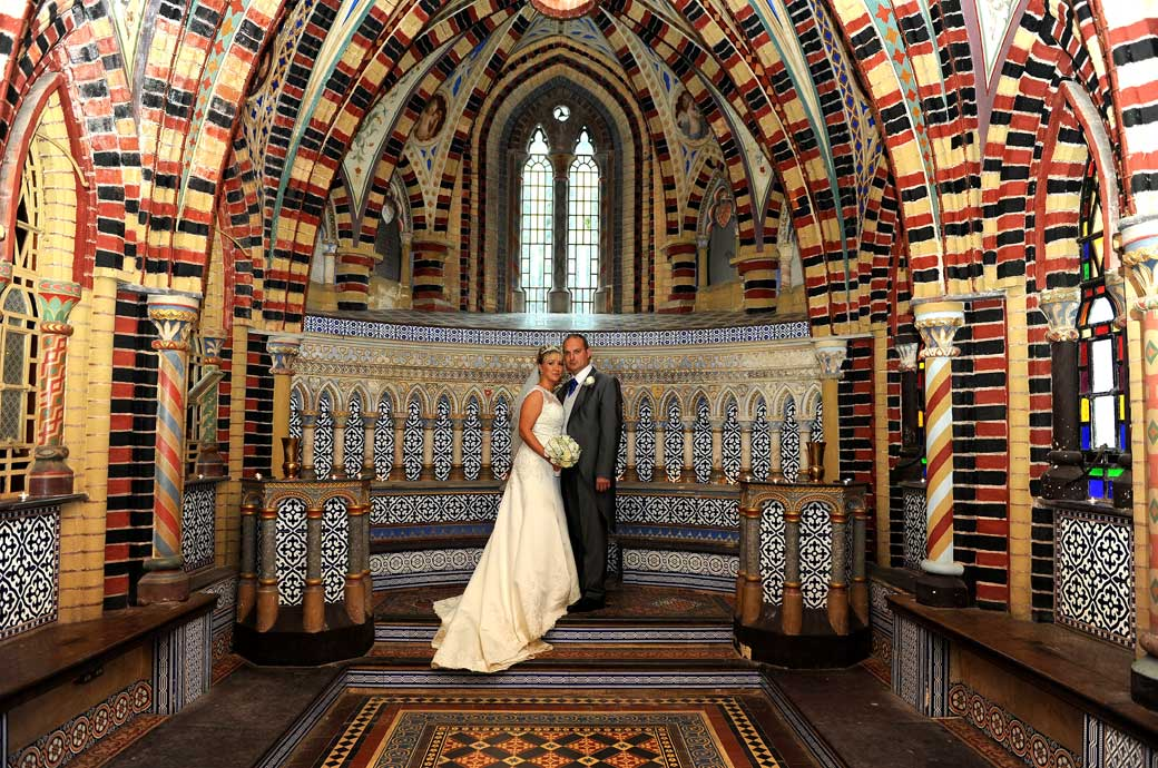 Newly-weds standing in front of the blue ceramic tiled area of the multi-coloured chapel in this wedding photograph taken in the fascinating Surrey wedding venue Horsley Towers