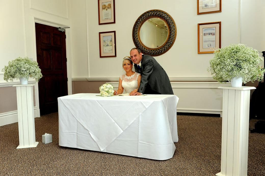 A happy handsome newly-wed couple pose for the guests' cameras as they sign the marriage register in the Sopwith Room at Horsley Towers captured by Surrey Lane wedding photography