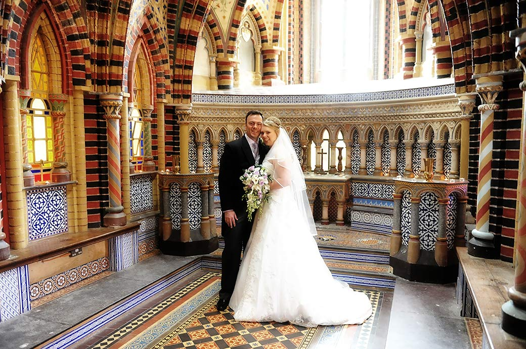 Bride and groom at Surrey wedding venue Horsley Towers standing together in the wonderfully colourful and elaborately tiled chapel
