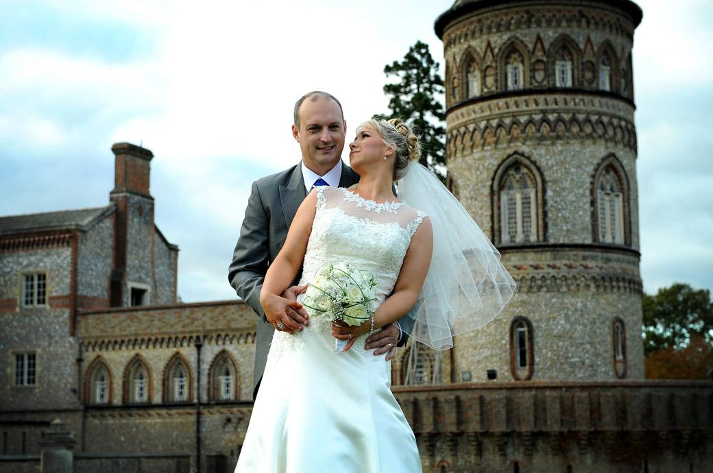 Romantic wedding photo of the Groom holding his wife as she looks up into his eyes on the small hill in front of the impressive Horsley Towers captured by Surrey Lane wedding photography