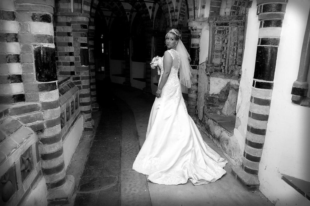 A beautiful Bride looking over her shoulder in this wedding photograph taken in the chapel cloisters at the fascinating and eccentric Surrey wedding venue Horsley Towers