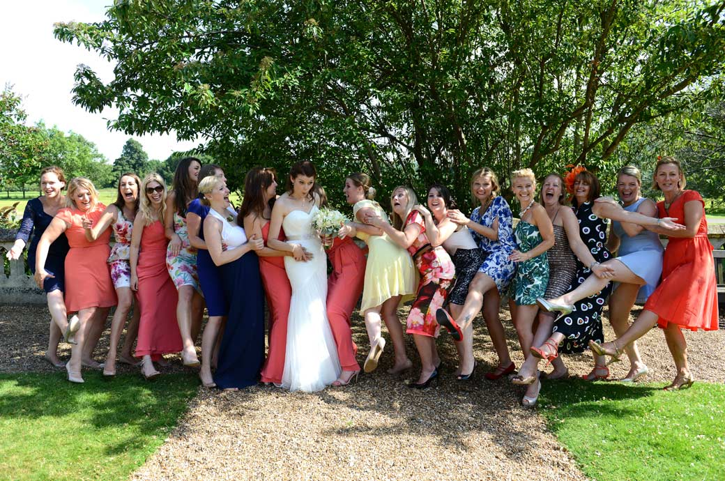Bride and the ladies pull faces as they almost fall over posing for this funny wedding photo taken at Horsley Towers by a Surrey Lane wedding photographer