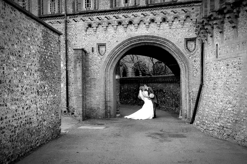 Passionate romantic Bride and Groom kissing wedding photo captured in an archway at the front of the wonderfully eccentric Surrey wedding venue Horsley Towers