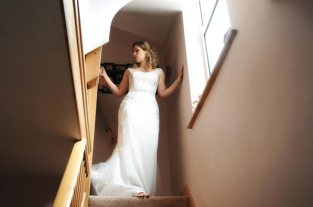 Beautiful bride looking stunning in her wedding dress as she descends the stairs at home on route for the world famous Surrey wedding venue Kew Gardens in Cambridge Cottage