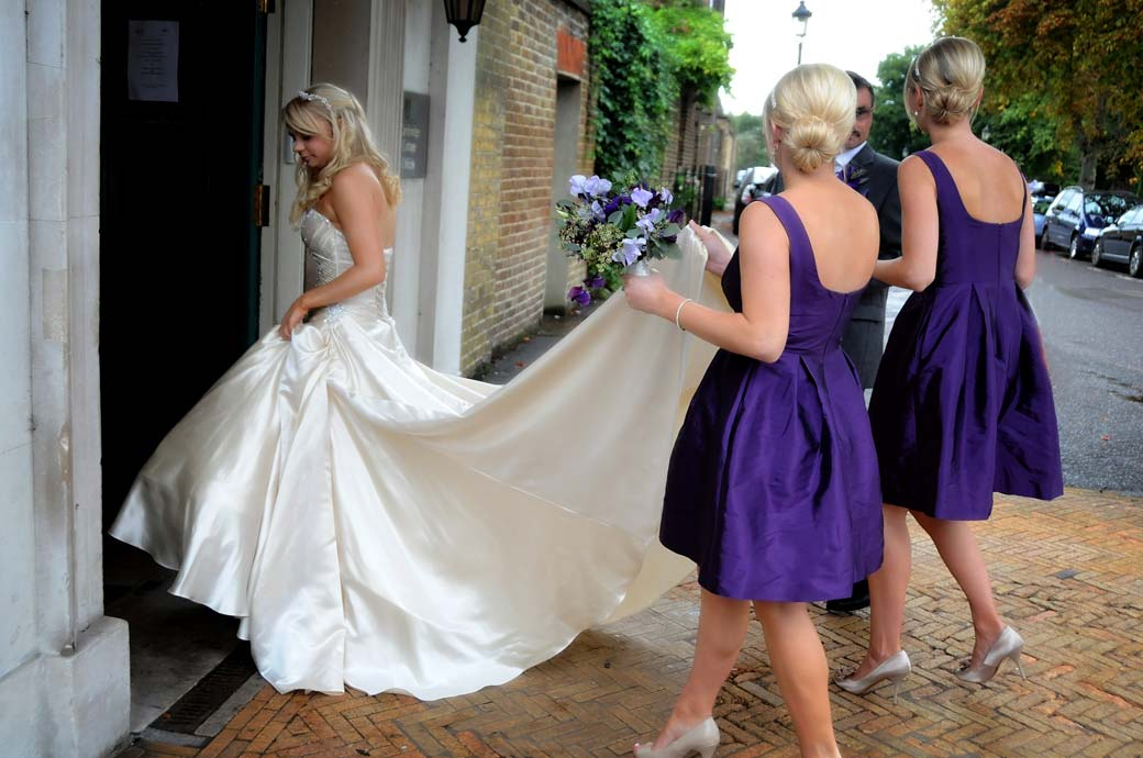 A wedding photograph of Bridesmaids in purple holding up the Bride's dress as she enters the Surrey wedding venue Cambridge Cottage in  Kew Gardens