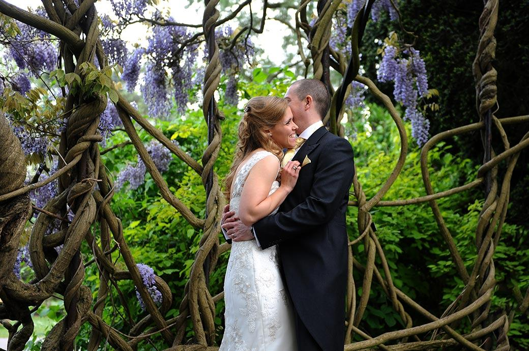 Hug of joy as the Bride and Groom celebrate their marriage in Cambridge Cottage by standing inside the amazing Wisteria tree located in Kew Botanical Gardens Surrey