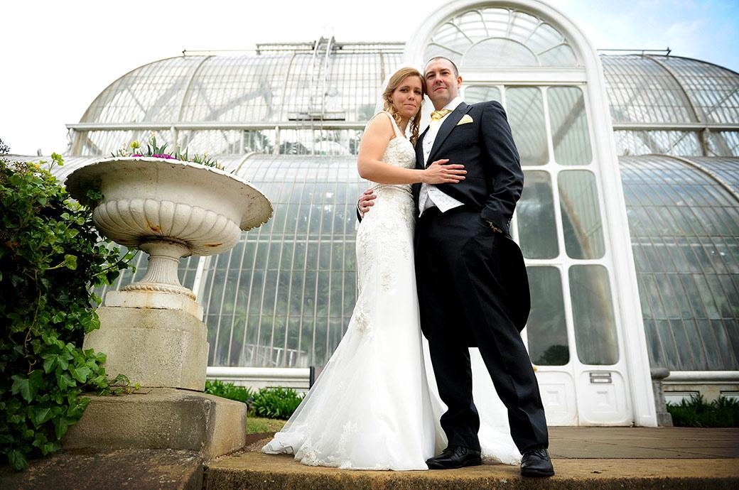 Wedding picture of a proud groom with his beautiful wife as they stand in front of the Palm House at the unique Surrey wedding venue Kew Gardens