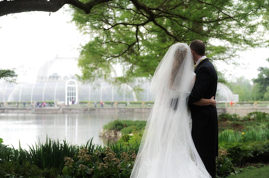 Romantic wedding photograph of a Bride and groom looking across the pond to the famous Palm House in Kew Gardens Surrey