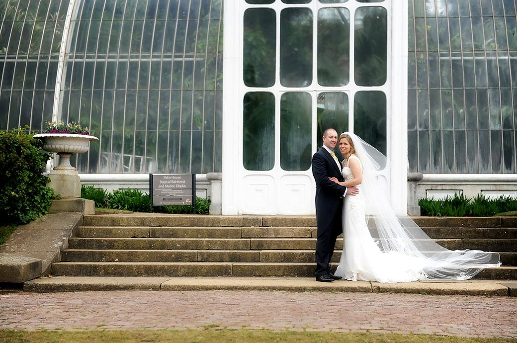 Happy Bride and groom at world famous Kew Gardens and Surrey wedding venue holding each other and smiling as they stand on the steps of the Palm House
