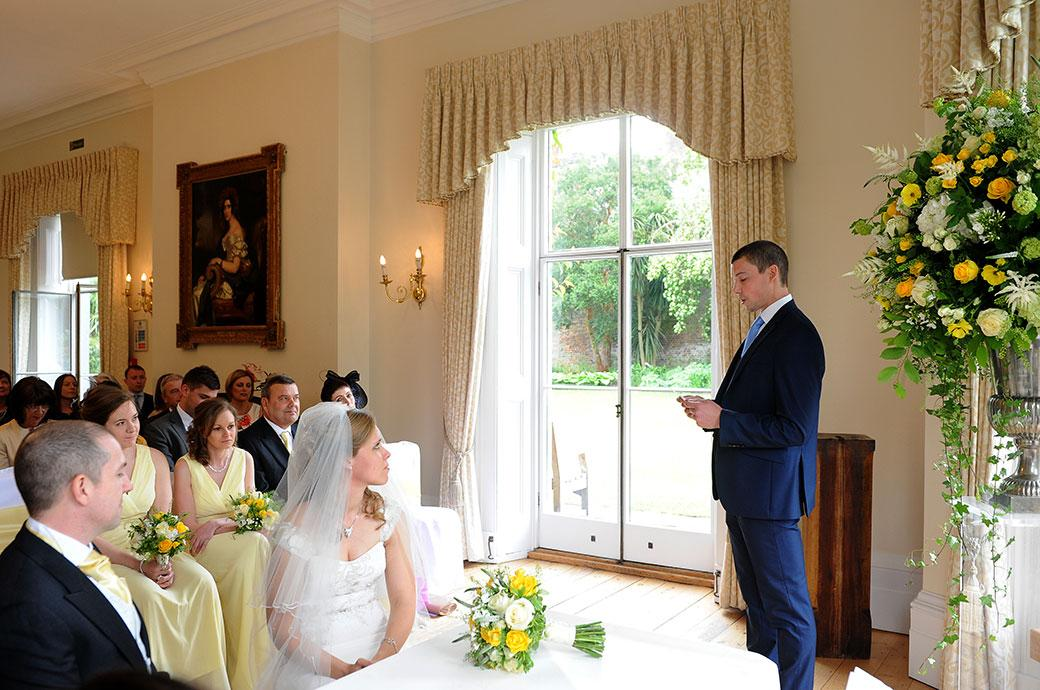 The Bride and groom listen attentively to a reading during the marriage ceremony at Surrey wedding venue Kew Gardens Cambridge Cottage in the Drawing Room