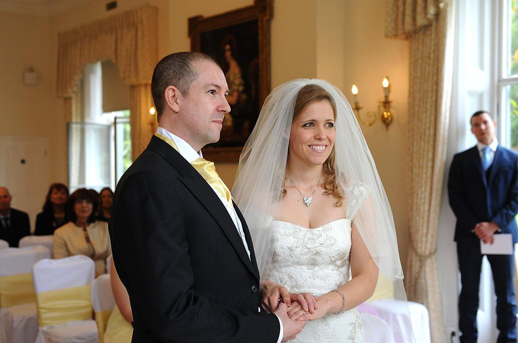 Happy smiling newlywed couple holding hands as they listen to the marriage registrar  in the Drawing Room at Surrey wedding venue Kew Gardens Cambridge Cottage