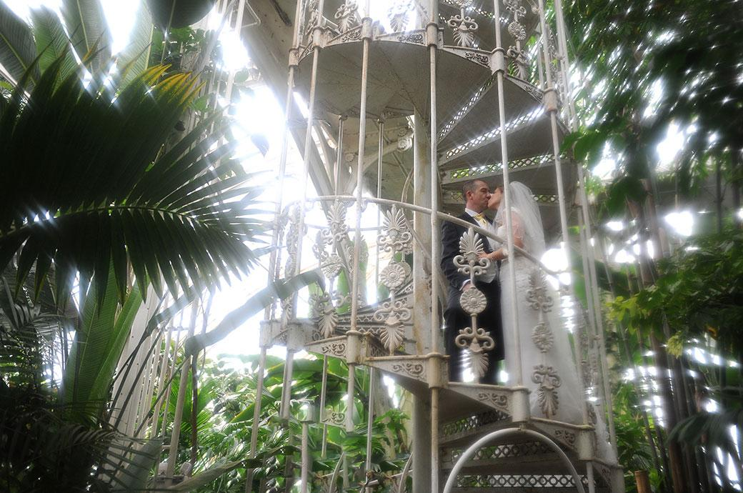 Bride and groom romantically kissing on the wrought iron spiral staircase inside the Palm House at the world famous Kew Gardens and unique Surrey wedding venue