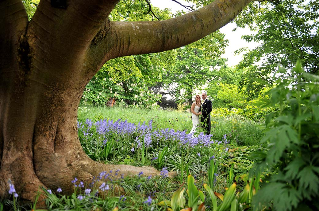 Beaming happy Bride and groom holding hands in the woods beyond the bluebells captured in Kew Gardens after their marriage at Surrey wedding venue Cambridge Cottage