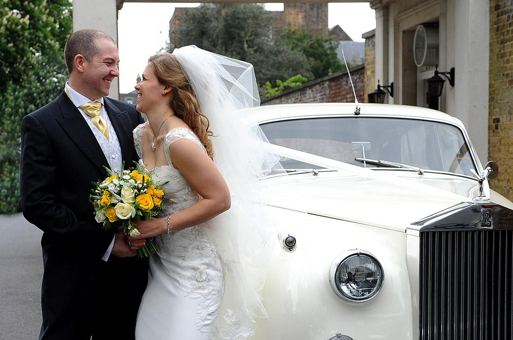 Newlyweds standing by their white Rolls Royce looking at each other and laughing with excitement outside the world famous Kew Gardens Cambridge Cottage in Surrey