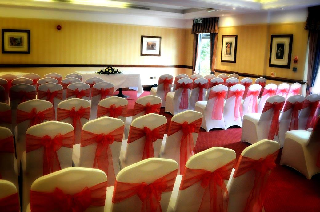 The ceremony room chairs dressed in red wedding photo taken at the Brook Kingston Lodge Hotel a Surrey wedding venue